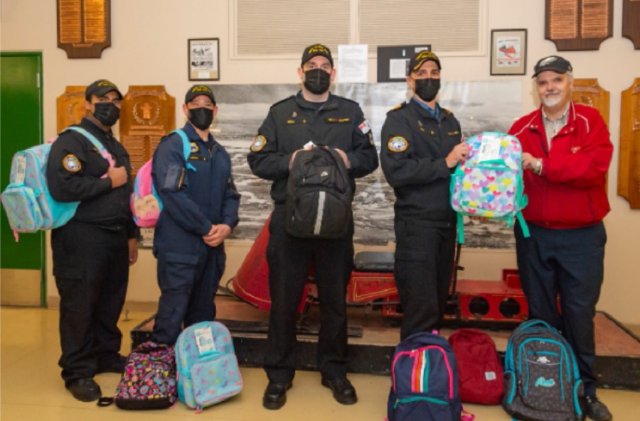 Royal Canadian Navy and Canadian Armed Forces personnel arrived in Iqaluit on the HMCS Goose Bay this week with backpacks and school supplies destined for students at Aqsarniit, Joamie and Nakasuk schools. Here, Navy and Armed Forces members (from left) Marcos Tinoco-Naar, Thomas Hodgin, Kevin Snow and Daniel Rice pose with Iqaluit District Education Authority chair Doug Workman Aug. 28. Halifax sailors, their families and local businesses donated 92 backpacks and $1,000 worth of school supplies to schools in Iqaluit and other communities in Nunavut. (Photo by Jaclyn Buell)