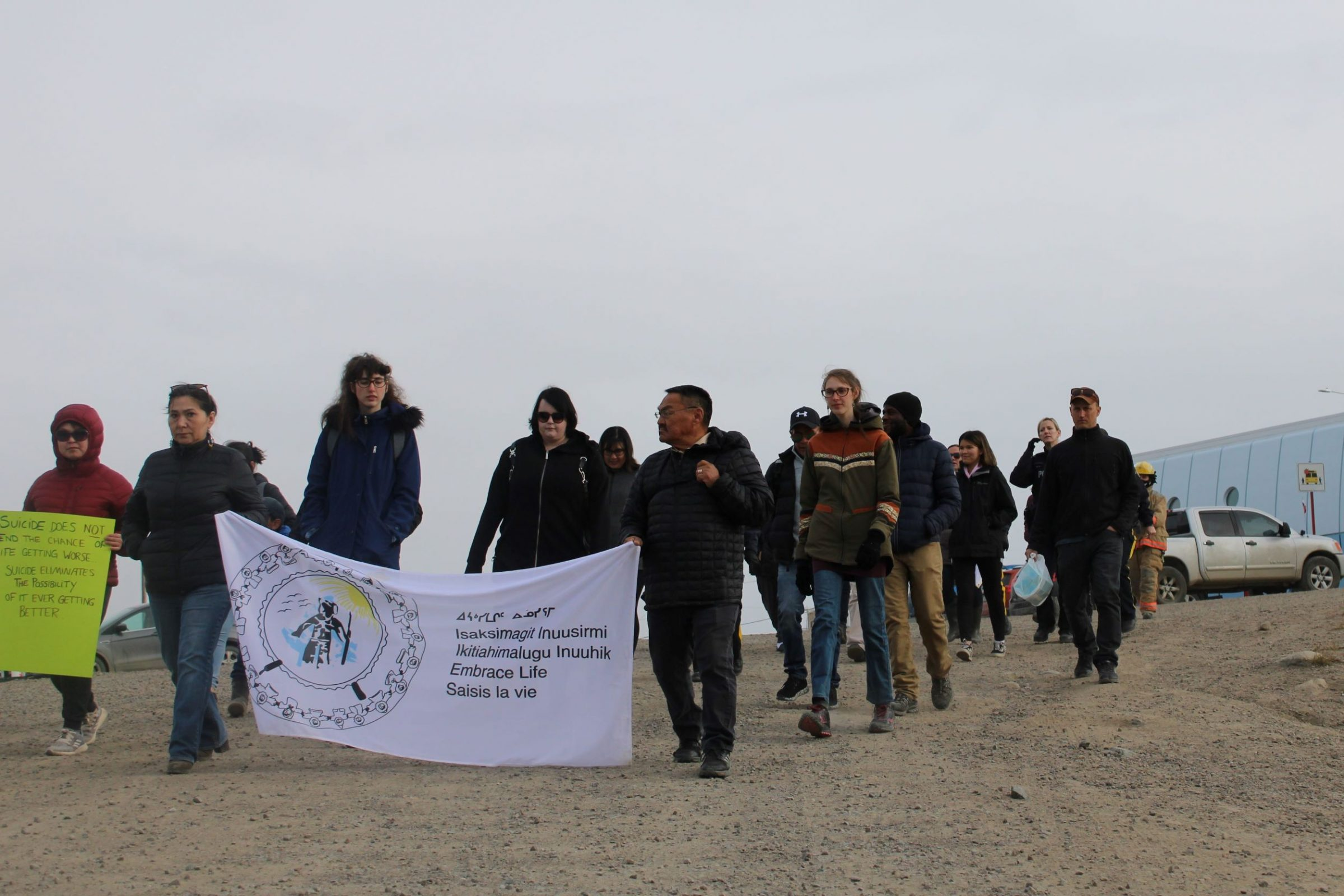 Iqaluit residents kick off the Embrace Life Day walk outside Inuksuk High School on Friday afternoon. The walk, organized by the Embrace Life Council, is dedicated to suicide prevention. Around 25 residents participated, following a route from the high school to the Four Corners before finishing at Iqaluit Square. (Photo by David Lochead)