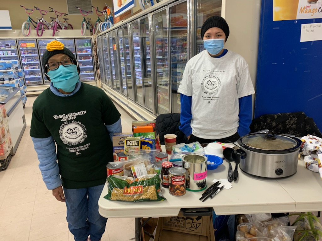 """Lucky Baker Lake residents were treated to caribou stew and fresh bannock last week when Annie Anautalik (left) and Aliyak Innakatsik (right) handed out food at the local Northern and Co-op stores. The initiative was run on Oct. 7 to promote the Baker Lake Prenatal Nutrition Project's programming, which is starting back up after a pandemic-related break in in-person classes. The organization helps expectant mothers and new mothers have healthy pregnancies and babies through educational programming. """"[The ladies] attracted the attention of many Baker Lakers who came to get a taste of the food and learn about our program,"""" Valerie Dorey, the program coordinator said. """"A delicious success for everyone,"""" she said. (Photo courtesy of the Baker Lake Prenatal Nutrition Project)"""