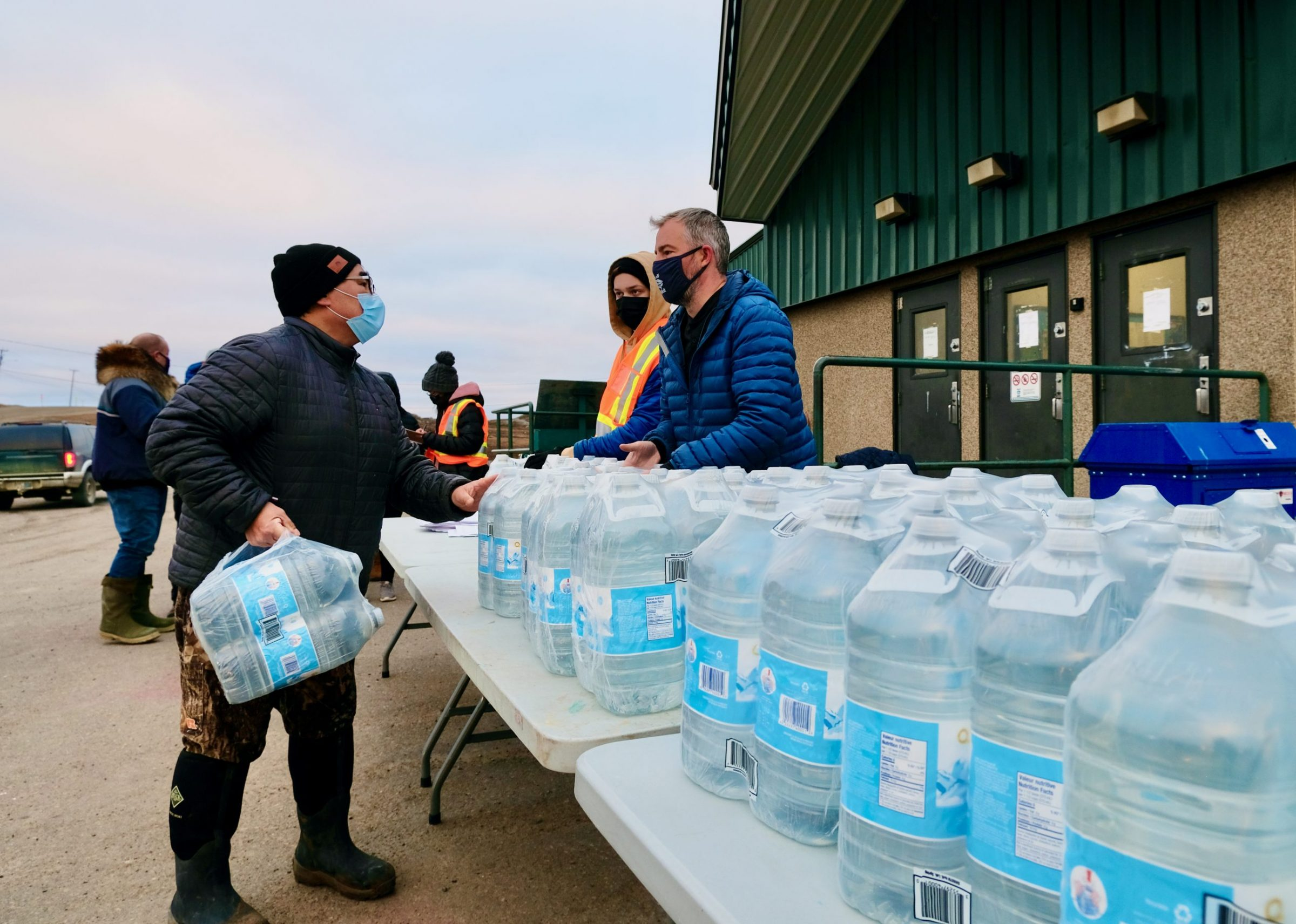 Iqaluit Mayor Kenny Bell, right, helps distribute jugs of water at the Arctic Winter Games Arena parking lot on Thursday, following the arrival of several thousand litres of of drinkable water on an afternoon flight. There is a second water distribution centre set up at the Arnaitok Arena parking lot. Both centres are open from 3:30 p.m. until 8 p.m. Residents are able to take four litres per household. Residents were told earlier in the week to not drink tap water because of potential fuel contamination. (Photo by Mélanie Ritchot)