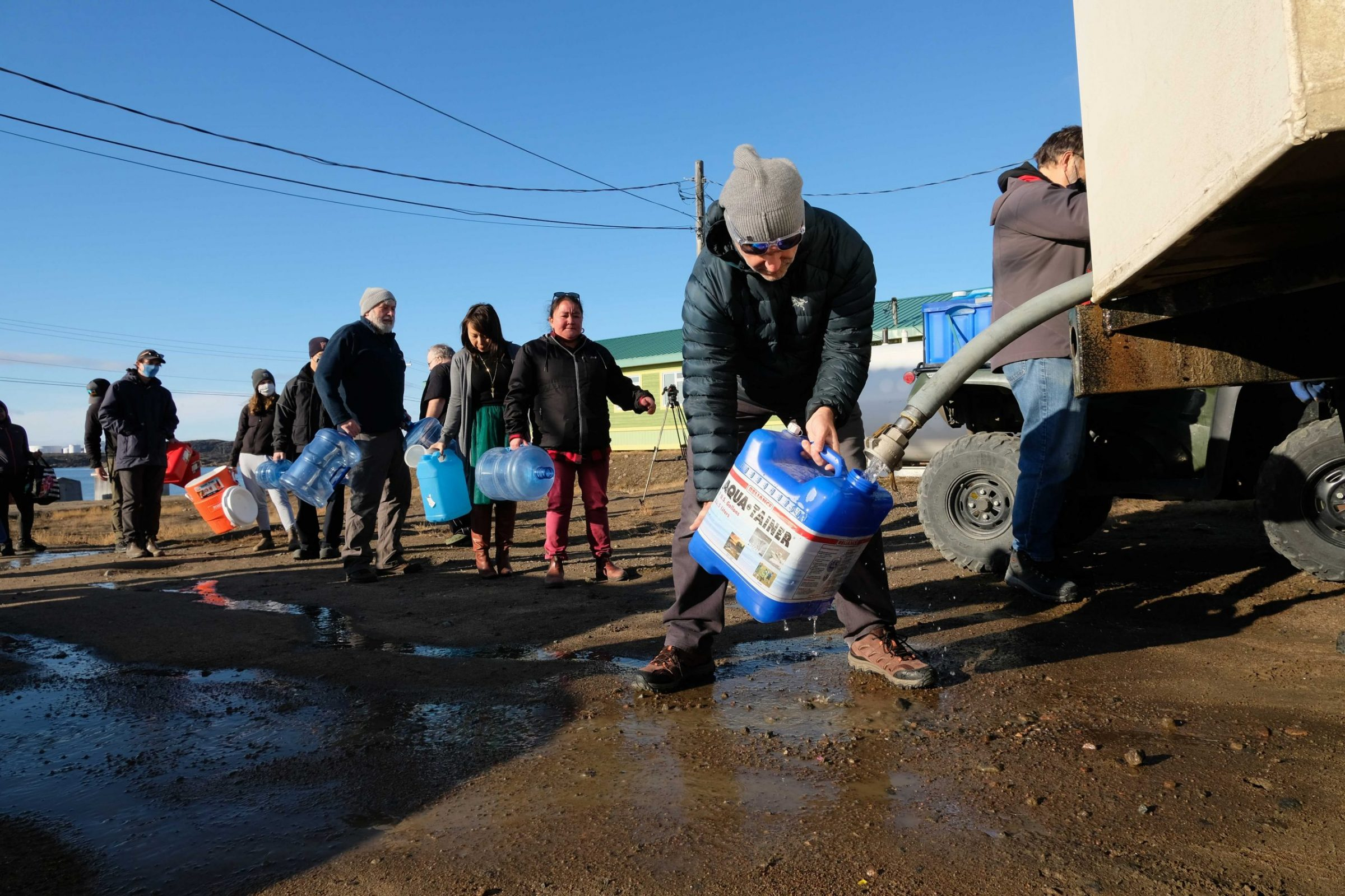 About 50 Iqaluit residents line up with water jugs at a fill station by the library around 11:30 a.m. Wednesday, following the arrival of the first water truck of the day. The water at the fill station is being pumped from a nearby river, following Tuesday's announcement that the city's tap water may be contaminated by fuel. Residents are being advised to not drink tap water, and to boil water from the river before drinking it. (Photo by Mélanie Ritchot)